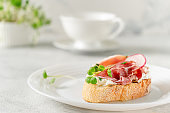 Mediterranean appetizer. Open sandwich with prosciutto or jamon on white plate. Copy space