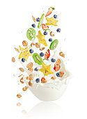 Fresh fruits, berries, corn flakes and nuts falling into the bowl with splashing milk. Healthy muesli breakfast concept.