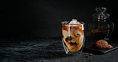 Iced coffee with cream on dark stone background. Copy space