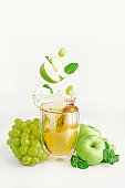Apple, grape and mint flying over the glass of splashing juice. Biological foods concept.
