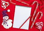 Empty Christmas wish list blank with candies and snowman on red background. Top view, mockup