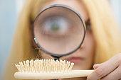 Woman magnifying hair brush