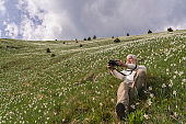Man photographing daffodils in mountains of Slovenia