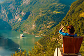 Tourist enjoy Geiranger fjord from viewpoint seat