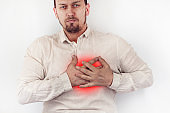 Feeling sick concept. A person has chest pain in the heart, highlighted in red, cropped