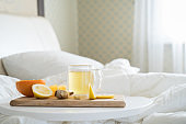 Cup with antipyretic drugs for colds,flu.Tea with citrus vitamin C,ginger root,lemon,orange.Wooden tray in patient's bed. Home self-treatment.Medical quarantine antiviral covid-19 coronavirus therapy