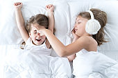 Little girls sleep in bed. One is snoring hard,sister is plugging ears with fur headphones.Early morning wake up,rise to kindergarten,school. Bedtime,sweet dreams.Kids correct daily routine for child