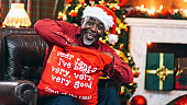 Senior afro men with santa hat drinking coffee in front of christmas tree and holding a christmas gift bag