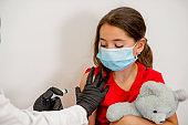 Pediatrician makes vaccination to cute schoolgirl