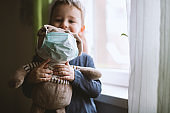 Child with teddy bear in protective medical masks. Prevention epidemic