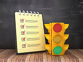 Check List Note Pad with Traffic Light on Chalkboard Background  - 3D Rendering