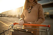 Young pregnant woman with shopping cart outdoors