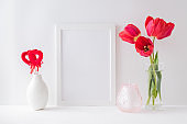 Home interior with decor elements. Mockup with a white frame, red tulips in a vase on a light background