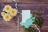 Mockup white wedding invitation and envelope with flowers in a vase on a wooden background