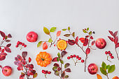 Flat lay pattern with colorful autumn leaves and apples on a white background