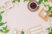 Flat lay composition with a cup of coffee and jasmine flowers on a color background