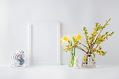 Home interior with easter decor. Mockup with a white frame and willow branches in a glass vase on a light background
