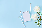 Flat lay blogger or freelancer workspace with a notebook and white peonies on a blue background