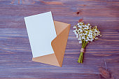Mockup white wedding invitation and envelope with white flowers on a wooden background