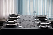 Table in the restaurant with empty plates and glass goblets.Empty table in the restaurant