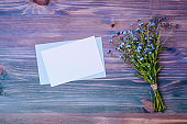 Mockup white wedding invitation and envelope with blue flowers on a wooden background
