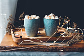 Hot chocolate with marshmallows and cinnamon in blue ceramic cups on a table. The concept of cozy holidays and New Year.