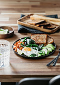 Healthy breakfast or lunch at home or cafe with fried egg, avocado, toasts, beans and fresh spinach on a wooden table.