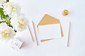 Mockup wedding invitation and envelope with white peonies on a white background