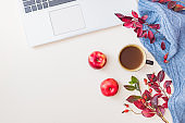 Flat lay home office desktop with colorful autumn leaves, laptop and a cup of coffee on a white background