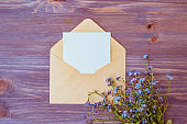 Mockup white wedding invitation and envelope with blue flowers on on a wooden table