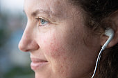 Close Up Side View of a Hopeful Woman Listening to Headphones