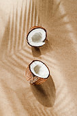 Summer abstract creative composition with coconut a on wooden tray over kraft paper.