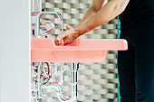 Woman rubbing hands while washing in red sink