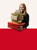 Smiling woman with stack of Christmas presents