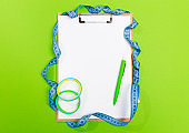 Healthy eating plan, diet or fitness planning, blank white paper on clipboard with measuring tape on green   background, writing message to set target or goal, menu or message.