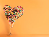Martini glass making heart shape with confetti