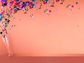 Flute spilling confetti on colored background