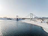 Bridge connecting two roads over a river in snow