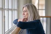 Sad blond woman watching through a window