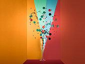 Close-up of champagne flute splashing confetti