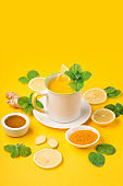 Lemon and ginger tea with honey on paper background.