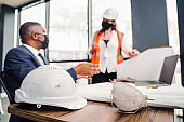 Hardhat and mask against professionals at office