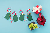 Festive winter holiday sale concept on blue paper background with Christmas gift boxes, tags and candy canes.
