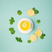 Herbal tea of chamomile flower with mint, lemon on paper blue background.