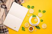 Herbal tea of chamomile flower with mint, ginger, lemon, honey on paper yellow background.