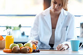 Woman nutritionist doctor working with her digital tablet for doing a diet plan in the consultation.