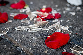 Violence in bad romance Valentine's day concept. Spoiled petals of roses and broken glass on floor after fight.