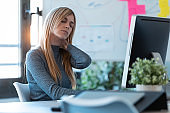 Tired business woman with neck pain looking uncomfortable while working with computer in the office.