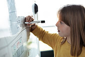 Little girl drawing on a whiteboard with a marker pen at home.