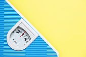 Blue weight scale on yellow background. Sport equipment. Healthy lifestyle and diet concept. Yellow and light blue. Copy space.